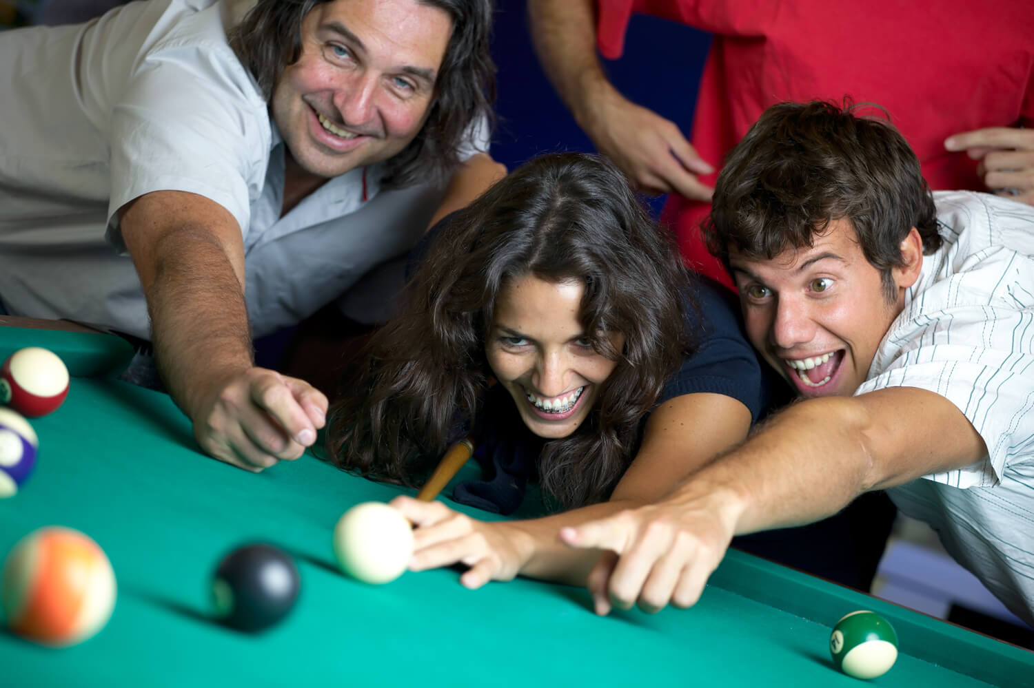 Smiling players having a game of pool on the home table