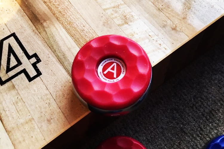 A shuffleboard puck hanging over the table