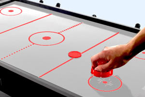 Air hockey played on the Trisport multi games table