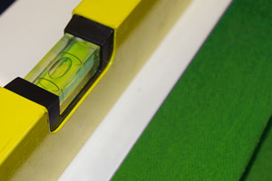 A spirit level being used to level the Olympus pool table