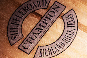 The Champion shuffleboard logo on a table