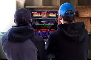 People experiencing playing Mortal Kombat 2 arcade.
