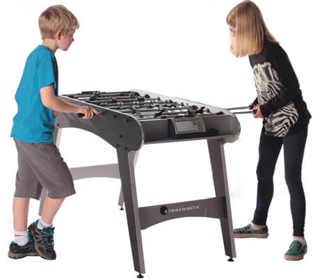 Children playing on a Defender football table.