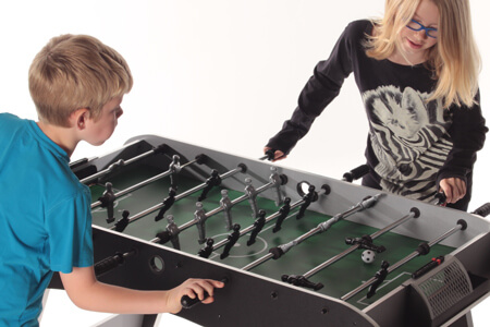 Kids playing on a Strikeworth Defender football table.